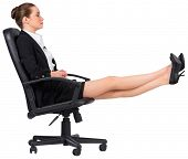 Businesswoman sitting on swivel chair with feet up on white background
