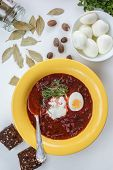 Red borscht soup in yellow plate from top