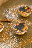Three Traditional Portuguese Egg Pies On A Wood Table With Cinnamon And Powder Sugar