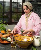Moroccan immigrant woman in modern European kitchen preparing traditional tajine dish for Ramadan nights