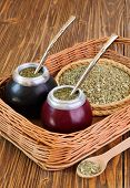 picture of calabash  - Yerba mate and mate in calabash on a wicker tray on a wooden background - JPG