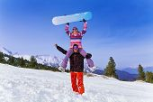 Happy snowboarder with woman on his shoulders