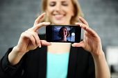 Young smiling woman making a self photo by her smartphone in office. Focus on smartphone