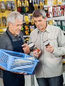 Senior salesperson assisting customer in buying pliers at hardware store