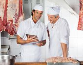 Portrait of confident butcher holding digital tablet while colleague looking at it in butchery