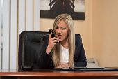 Angry Businesswoman Yelling Into A Cellphone