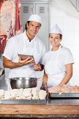 Portrait of confident butchers with digital tablet in shop