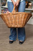 Low section of female customer carrying shopping basket in grocery store