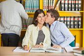 Loving young man kissing woman at table in college library