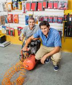 Portrait of smiling father and son holding air compressor in hardware store