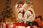 Christmas Family Portrait In Home Holiday Living Room, Kids And Baby At Santa Hat With Present Gift
