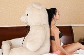 woman sitting back to back with a big teddy bear