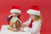 Festive little girls making a gingerbread house on red background
