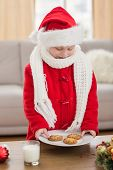 Festive little boy holding plate of cookies at home in the living room