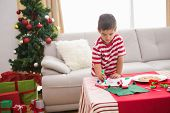 Cute boy drawing festive pictures at home in the living room