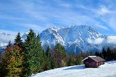 Hut On Snow Meadow In Winter Alps