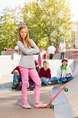 Blond girl in front with skateboard and friends