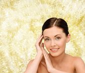 beauty, people and health concept - smiling young woman with bare shoulders over yellow lights background