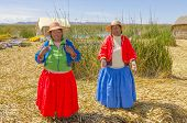PUNO, PERU, MAY 5, 2014: Uros islands on Titicaca lake - Local women sing welcoming tourists visiting islands