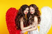 Two Attractive Fashion Women Wearing In Angel Costume With Wings Isolated On Yellow Background.