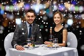 restaurant, christmas, holidays and people concept - smiling couple eating main course at restaurant over night lights background