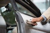 stock photo of open arms  - Close up of human male hand opening car door - JPG