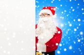 christmas, holidays, advertisement and people concept - man in costume of santa claus with white blank billboard making hush gesture over blue snowy background