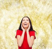 christmas, holidays, valentine's day, celebration and people concept - smiling woman in red dress over yellow background