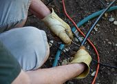 Homeowner Works On Sprinkler System