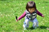 Small two years old chinese girl play on the grass with feather in hand.
