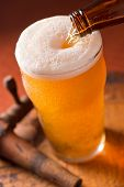 stock photo of keg  - A glass of cold beer being poured on top of a rustic keg with antique spigot - JPG