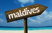 Maldives wooden sign with a beach on background
