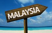 Malaysia wooden sign with a beach on background