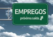 Empregos, proxima saida (Jobs, next exit in portuguese) creative road sign and clouds