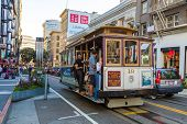 SAN FRANCISCO, CA - SEP 20: Passengers enjoy a ride in a cable car on September 20, 2013 in San Francisco. It is the oldest mechanical public transport in San Francisco which is in service since 1873.