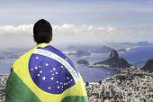 Brazilian holding a brazilian flag looks to the beautiful view of Rio de Janeiro, Brazil