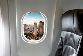Buildings through aircraft window onto jet engine