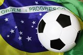 stock photo of bandeiras  - Soccer ball and the flag of Brazil - JPG