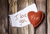 I Love You Mom written on a peace of paper and a heart on a wooden background