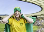 Woman holds a brazilian flag on the stadium