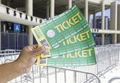 Hand holds soccer tickets in front of the Maracana Stadium