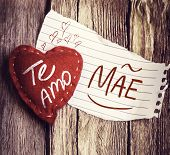 "stock photo of miss you  - ""Te Amo, Mae"" (In portuguese - Love You, Mother) written on a peace of paper and a heart on a wooden background - JPG"