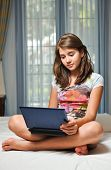 Young teen girl sitting on her bed surfing the internet