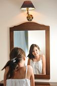 foto of mirror  - A beautiful teen girl studies her appearance as she looks into the mirror at her beautiful young reflection - JPG