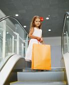 Beautiful little girl in dress with shopping bag