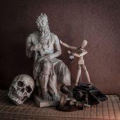 Still Life Of Moses Statue ,skull,wooden Figure On Mat