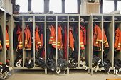 stock photo of medevac  - Firefighter suits hanging in a row at the station - JPG