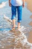 Barefoot Man In Jeans Walking On The Sea Shore