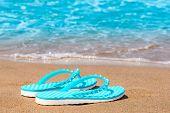 Turquoise Flip Flops Abandoned On A Sandy Seashore