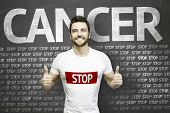 stock photo of causes cancer  - Campaign against Cancer by a man on blackboard background - JPG
